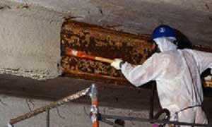 Asbestos Worker working on beams